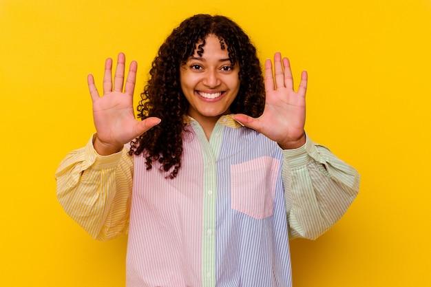 Молодая женщина смешанной расы, изолированные на желтом фоне, показывая номер десять руками.