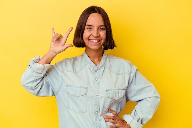 指でロック ジェスチャーを示す黄色の背景に分離された若い混血女性