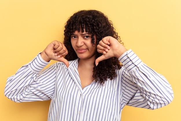 Молодая женщина смешанной расы, изолированные на желтом фоне, показывая большой палец вниз, концепция разочарования.