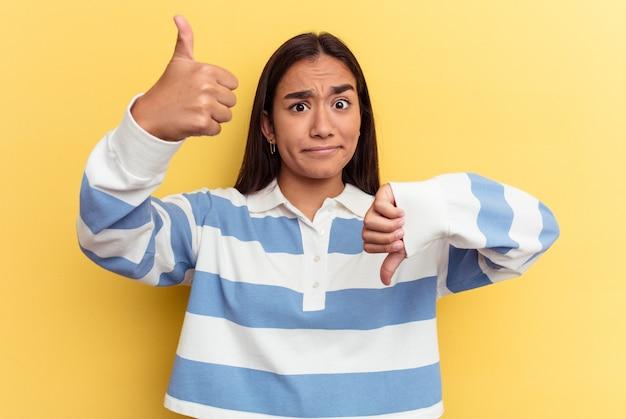 親指を上と親指を下に示す黄色の背景に分離された若い混血の女性、難しい選択の概念