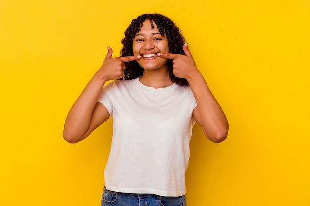 입에서 손가락을 가리키는 노란색 배경 미소에 고립 된 젊은 혼합 된 인종 여자.