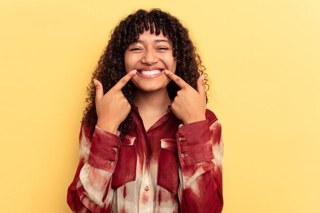 노란색 배경에 격리된 젊은 혼혈 여성은 손가락을 입으로 가리키며 미소를 짓고 있습니다.