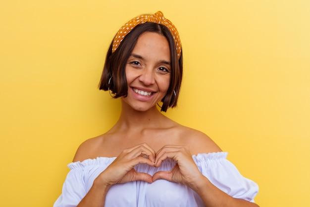 笑顔と手でハートの形を示す黄色の背景に分離された若い混血の女性。