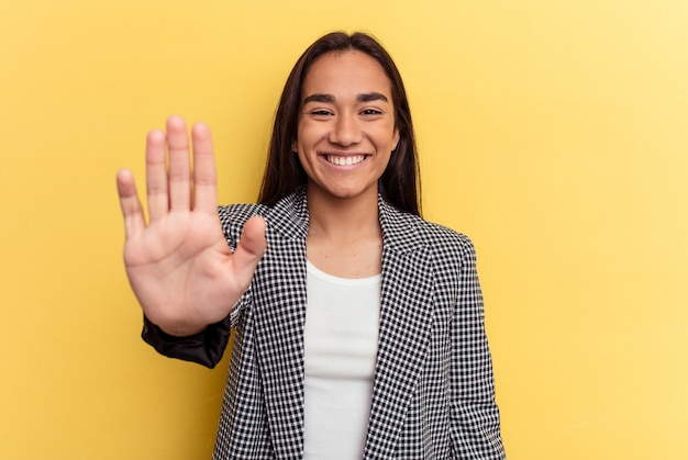 黄色の背景に分離された若い混血の女性は、指で5番を示して陽気に笑っています。
