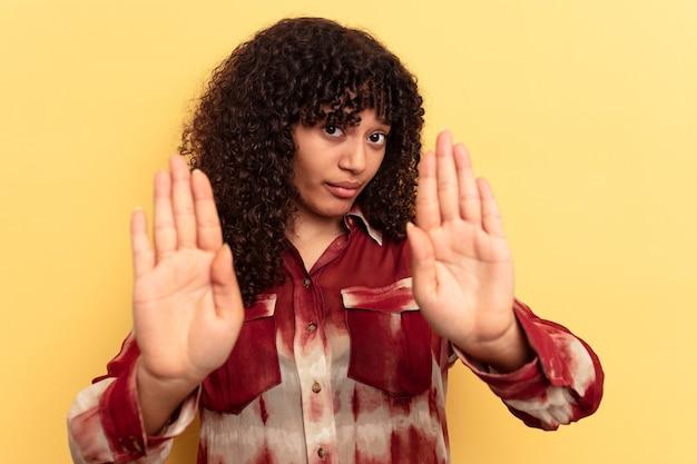 Молодая женщина смешанной расы, изолированные на желтом фоне, стоя с протянутой рукой, показывая знак остановки, предотвращая вас.