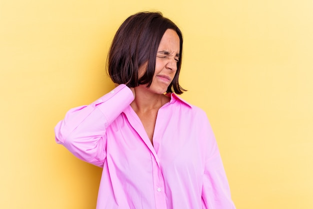 Молодая женщина смешанной расы, изолированная на желтом фоне, страдает от боли в шее из-за малоподвижного образа жизни.