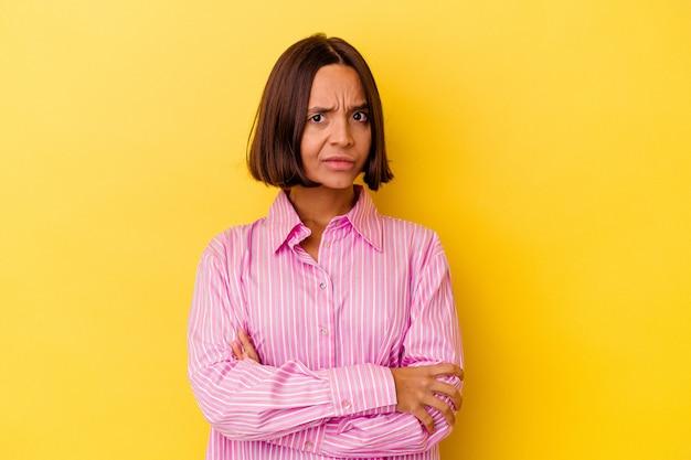 Молодая женщина смешанной расы, изолированные на желтом фоне, подозрительно, неуверенно, исследует вас.