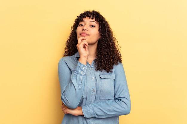 黄色の背景に孤立した若い混血の女性は、疑わしい、不確かな、あなたを調べています。