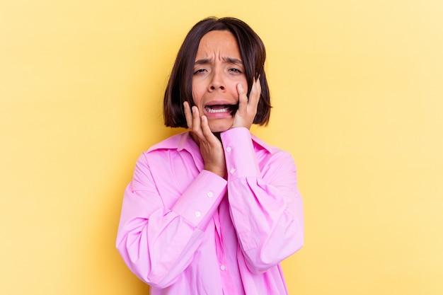 Молодая женщина смешанной расы, изолированные на желтом фоне, безутешно ныть и плакать.