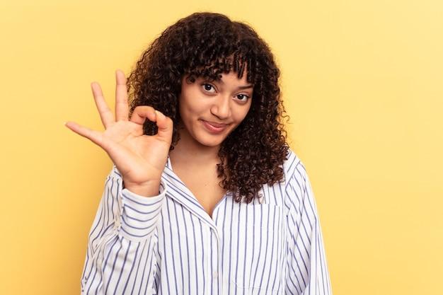 노란색 배경에 고립된 젊은 혼혈 여성은 눈을 윙크하고 손으로 괜찮은 몸짓을 합니다.