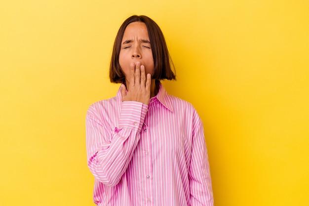 黄色の背景に分離された若い混血の女性は、手で口を覆っている疲れたジェスチャーを示すあくびをしています。