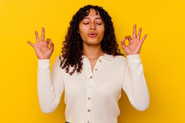 Молодая женщина смешанной расы, изолированная на желтом, расслабляется после тяжелого рабочего дня, она выполняет йогу.