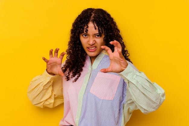 黄色で隔離された若い混血の女性は、猫を模倣した爪、攻撃的なジェスチャーを示しています。