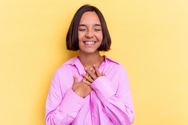 노란색 벽에 고립 된 젊은 혼혈 여자는 큰 소리로 가슴에 손을 유지 웃음.
