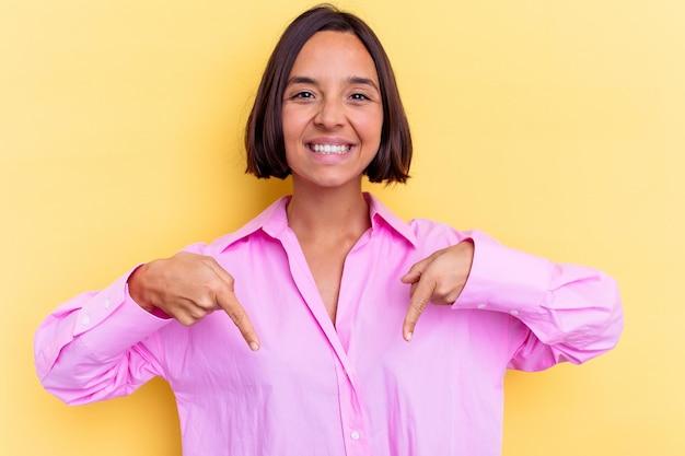 노란색 벽에 고립 된 젊은 혼혈 여자 손가락, 긍정적 인 느낌으로 아래로 가리 킵니다.