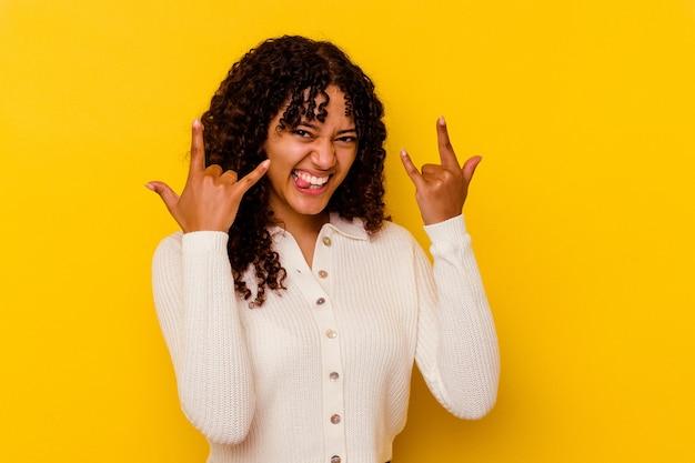 革命の概念として角のジェスチャーを示す黄色の壁に分離された若い混血の女性。
