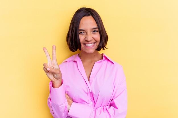 손가락으로 2 번을 보여주는 노란색 벽에 고립 된 젊은 혼합 된 인종 여자.