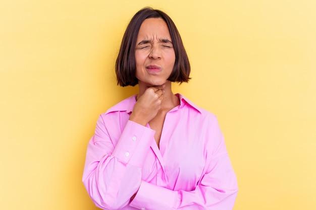 黄色の壁に隔離された若い混血の女性は、ウイルスや感染症のために喉の痛みに苦しんでいます。
