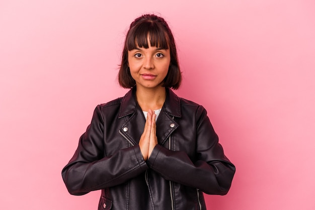 Young mixed race woman isolated on pink background praying, showing devotion, religious person looking for divine inspiration.