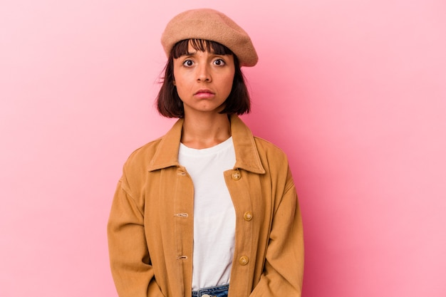 Young mixed race woman isolated on pink background sad, serious face, feeling miserable and displeased.