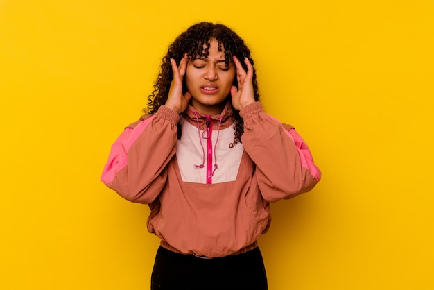 Young mixed race woman isolated on pink background touching temples and having headache.