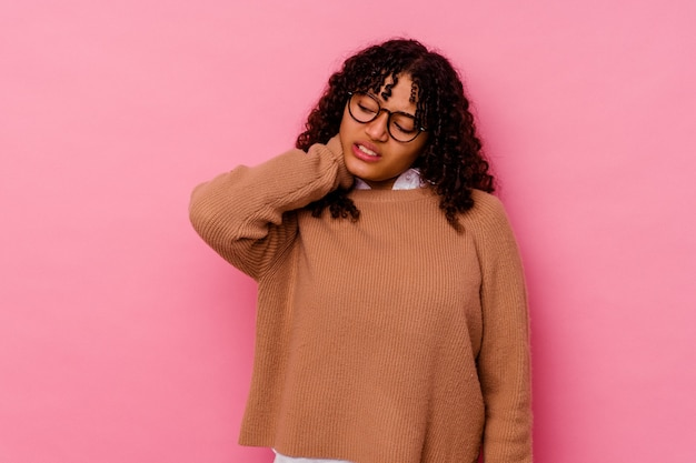 Young mixed race woman isolated on pink suffering neck pain due to sedentary lifestyle.