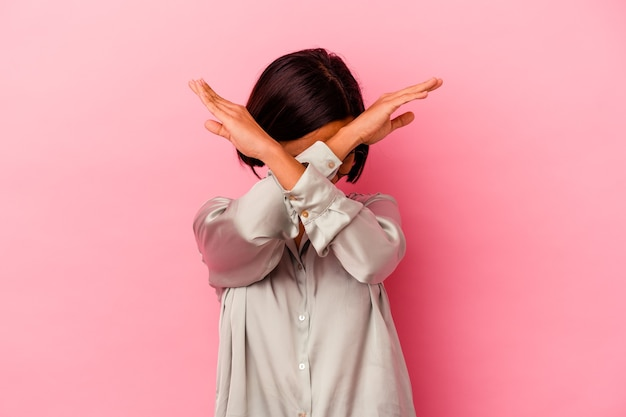 Young mixed race woman isolated on pink wall keeping two arms crossed, denial concept.