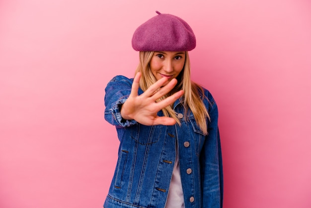 Young mixed race woman isolated on pink wall rejecting someone showing a gesture of disgust.