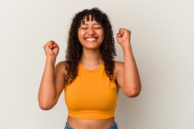 Young mixed race woman isolated on white background celebrating a victory, passion and enthusiasm, happy expression.