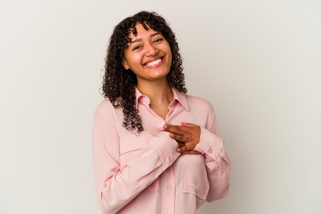 Young mixed race woman isolated on white background has friendly expression, pressing palm to chest. love concept.