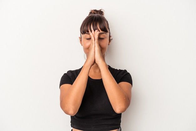Young mixed race woman isolated on white background  holding hands in pray near mouth, feels confident. Premium Photo