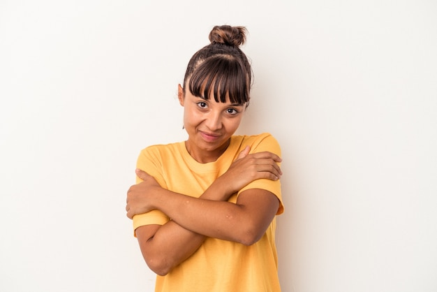 Young mixed race woman isolated on white background  hugs, smiling carefree and happy.