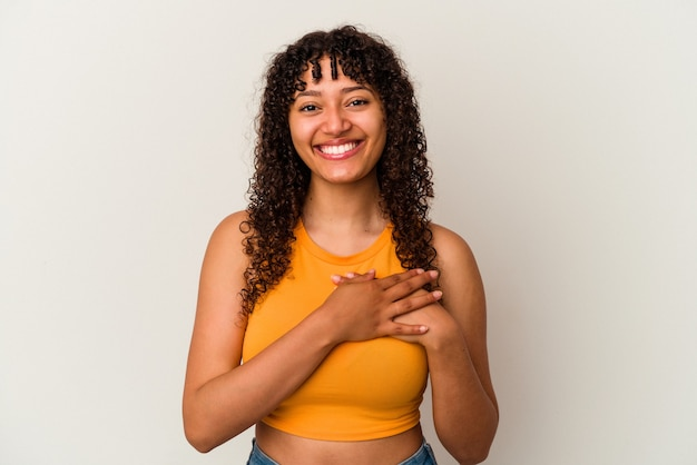 Young mixed race woman isolated on white background laughing keeping hands on heart, concept of happiness.