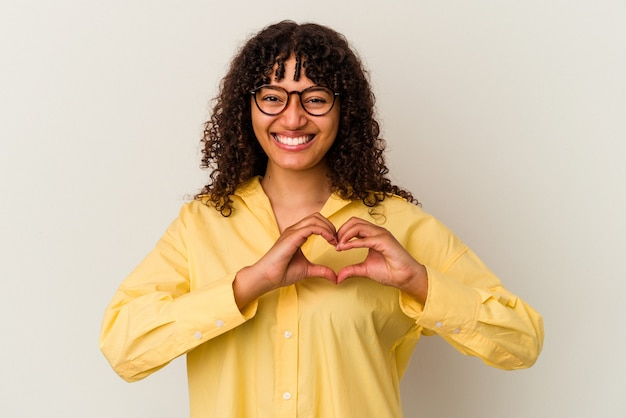 Young mixed race woman isolated on white background smiling and showing a heart shape with hands.