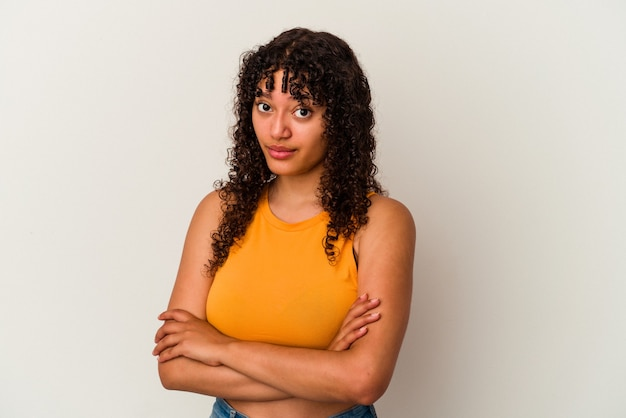 Young mixed race woman isolated on white background suspicious, uncertain, examining you.