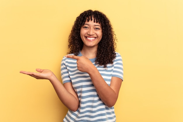 Young mixed race woman isolated on yellow background excited holding a copy space on palm.