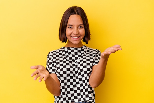 Young mixed race woman isolated on yellow background feels confident giving a hug to the camera.