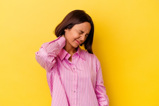 Young mixed race woman isolated on yellow background having a neck pain due to stress, massaging and touching it with hand.