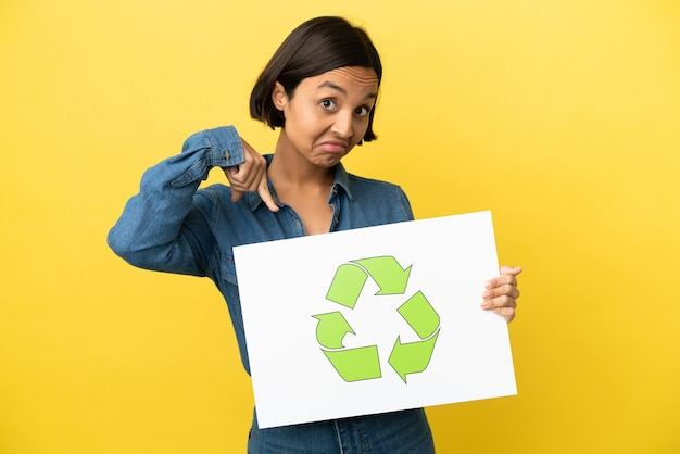 Young mixed race woman isolated on yellow background holding a placard with recycle icon and  pointing it