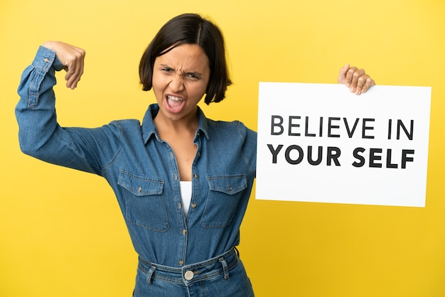 Young mixed race woman isolated on yellow background holding a placard with text believe in your self and doing strong gesture