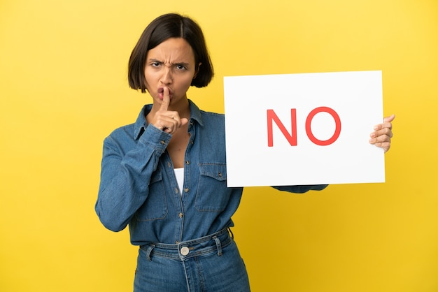 Young mixed race woman isolated on yellow background holding a placard with text no doing silence gesture