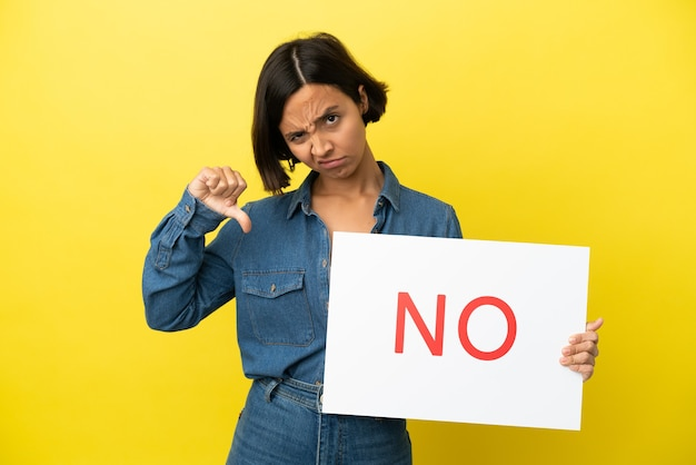 Young mixed race woman isolated on yellow background holding a placard with text no