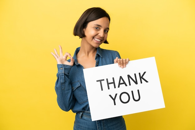 Young mixed race woman isolated on yellow background holding a placard with text thank you with ok sign