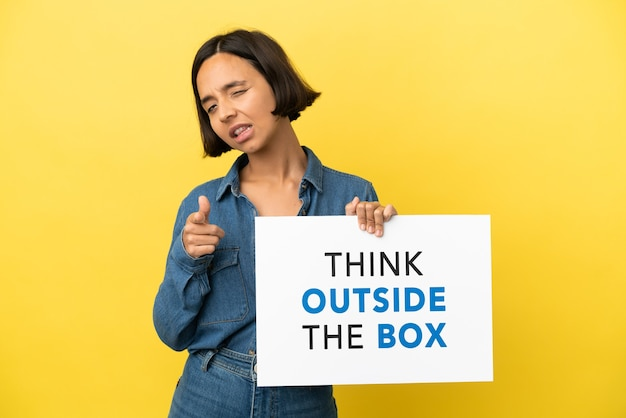 Young mixed race woman isolated on yellow background holding a placard with text think outside the box and pointing to the front