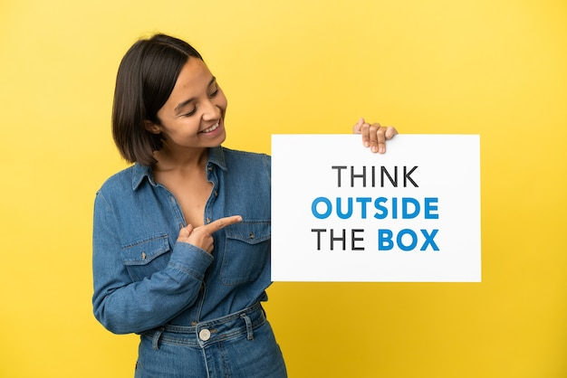 Young mixed race woman isolated on yellow background holding a placard with text think outside the box and  pointing it