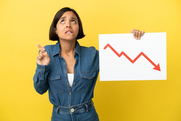 Young mixed race woman isolated on yellow background holding a sign with a decreasing statistics arrow symbol with fingers crossing