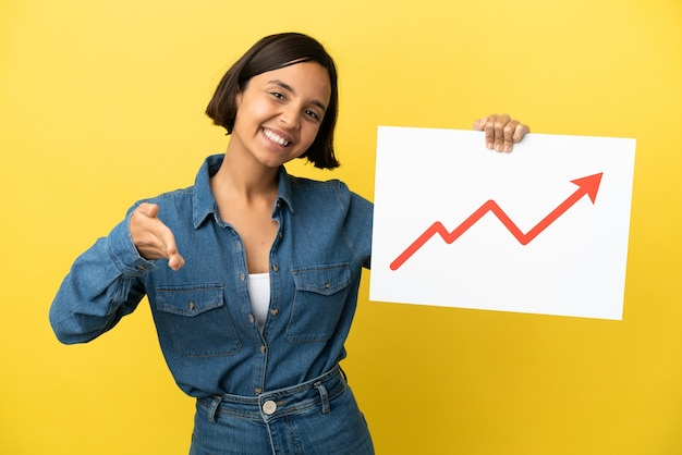 Young mixed race woman isolated on yellow background holding a sign with a growing statistics arrow symbol making a deal