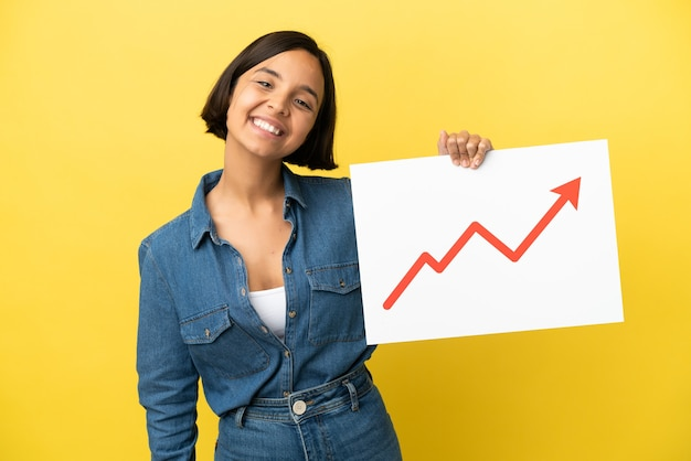 Young mixed race woman isolated on yellow background holding a sign with a growing statistics arrow symbol with happy expression