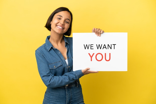 Young mixed race woman isolated on yellow background holding we want you board with happy expression