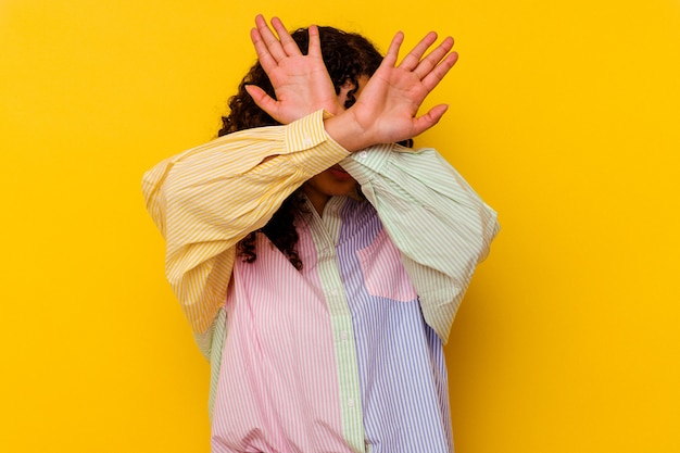Young mixed race woman isolated on yellow background keeping two arms crossed, denial concept.